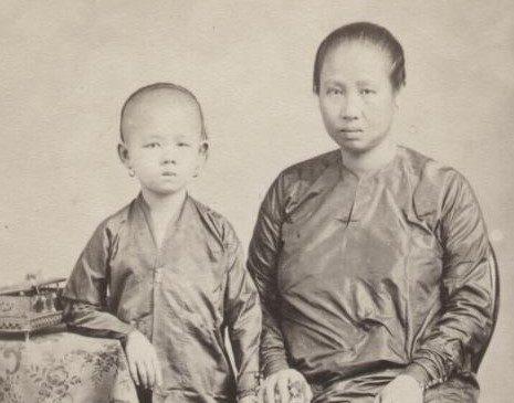 22 Tradities en Cultuut Baju panjang' met gingham (gestreepte of geruite katoen) sarong (links) en 'baju kurong' met batik sarong (rechts). Batavia, 1867. KITLV 87452