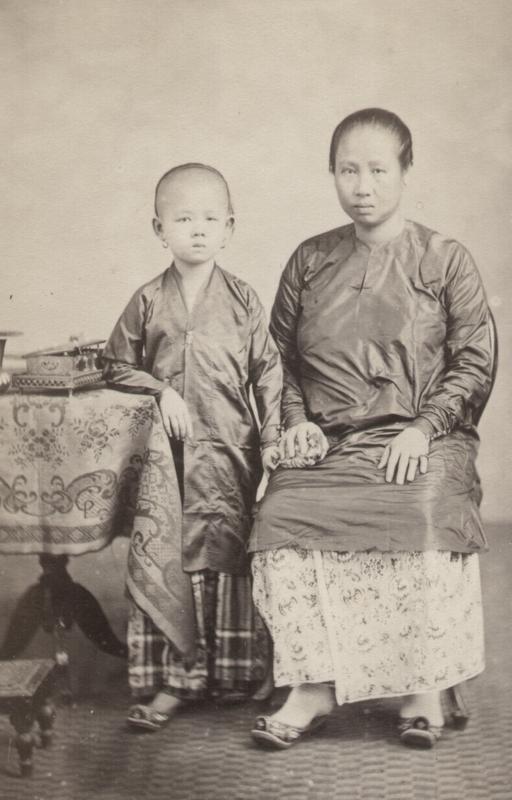 'Baju panjang' met gingham (gestreepte of geruite katoen) sarong (links) en 'baju kurong' met batik sarong (rechts).  Batavia, 1867. KITLV 87452. Volledige foto: zie onderaan.